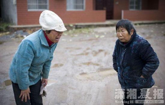 熊女士拿出女儿照片给邻居看。 图/长株潭报记者 陈杰