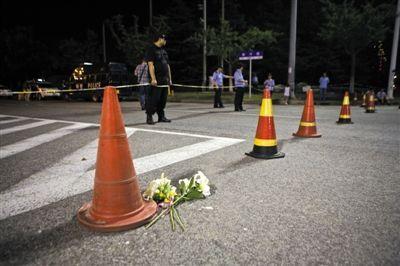昨日,昆山中荣金属制品有限公司爆炸现场警戒线外,几束花被放在地上。新京报记者 周岗峰 摄