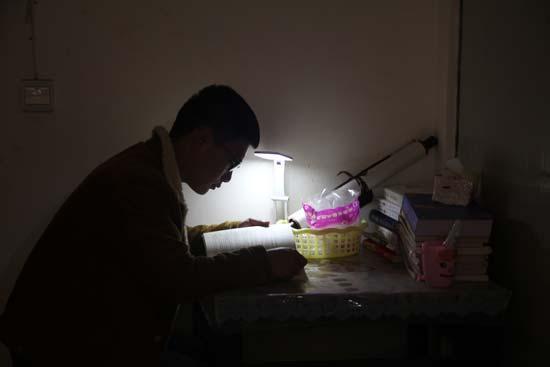 杨威在出租房里读书。贵州工程应用技术学院李佳丽/摄