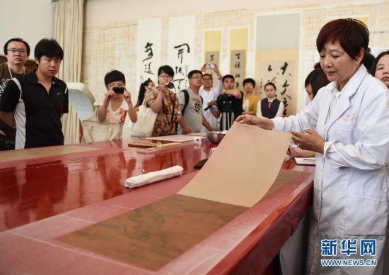 5月27日,首都博物馆书画装裱专家楼朋竹在展示利用生物揭展剂把一幅古书画的背纸轻松完整揭离。