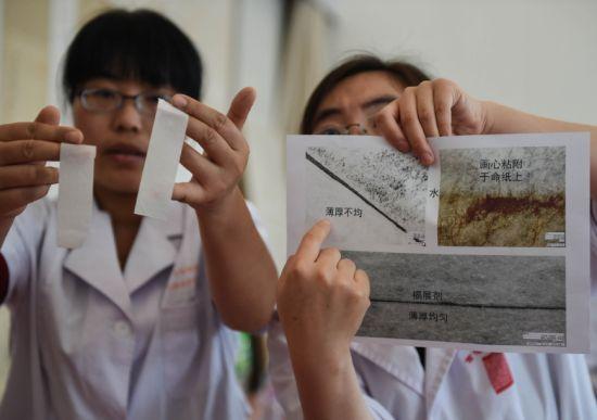 5月27日,首都博物馆的工作人员在展示在显微镜下观察到的利用生物揭展剂和传统揭展剂(水)对古书画作品进行揭展的对比效果。