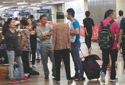 6月20日,北京西站,一男一女两医托(左一女子与灰衣男子)正忽悠母子俩去看专家。