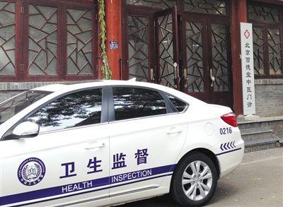 """昨日,""""卫生监督""""执法车辆停靠在""""百德堂""""诊所门外。诊所大门左侧""""北京中研汉唐中医药研究中心""""牌匾已被执法人员摘除。 本版摄影新京报记者 尹亚飞 摄"""