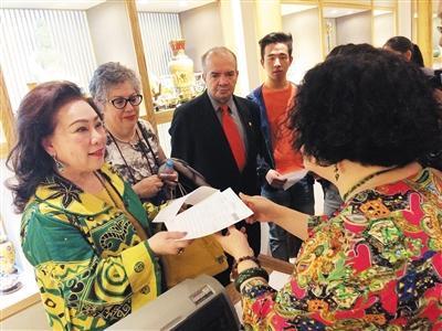 昨日上午,秀水街一家工艺品店内,印尼顾客钟家燕(左一)领到秀水街首张离境退税申请单。本版摄影/新京报记者 李婷婷
