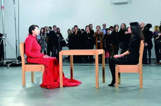 2010 年《艺术家在现场》 时长:736 小时30 分钟纽约MoMA 展厅里,阿布拉莫维奇坐在桌子一端,另一端是自愿坐到对面的观众。64 岁的阿布拉莫维奇接受了1500 多人的对视挑战,莎朗·斯通、Lady Gaga 亦慕名而来。她每天就这样面无表情地坐着。