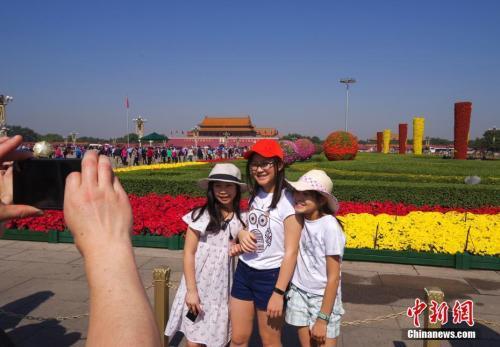 9月29日,三位小游客在北京天安门广场国庆花坛前留影。 中新社记者 贾天勇 摄
