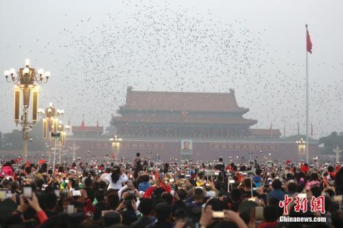 10月1日,民众在北京天安门广场观看国庆升旗仪式。中新社记者 盛佳鹏 摄