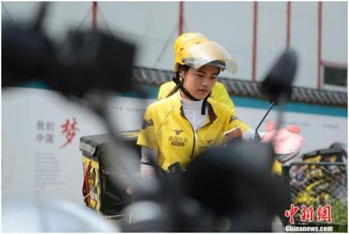 这五年,网络外卖催生了外卖送货员这一职业,大量骑着电动车穿梭在街头巷尾的外卖送货员成为城市的一道风景线。图为北京一位女送货员在送餐。中新网记者 富宇 摄