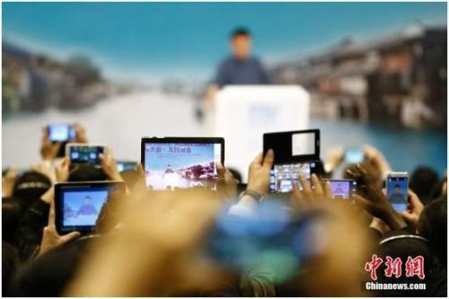 2015年12月18日,浙江乌镇,第二届世界互联网大会闭幕式上,与会者纷纷用手机进行拍摄。 中新社记者 盛佳鹏 摄