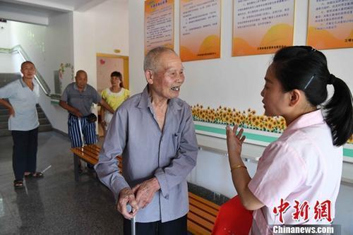 资料图:住在敬老院的老人向医护人员咨询保健常识。中新社记者 张斌 摄