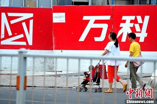 图为7月3日,福州民众从万科开发的房地产楼盘旁经过。 中新社记者 张斌 摄