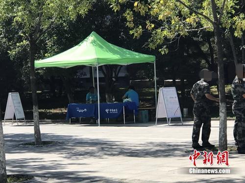 中国电信在某高校内摆摊出售手机卡,旁边就是正在军训的学生。中新网 吴涛 摄