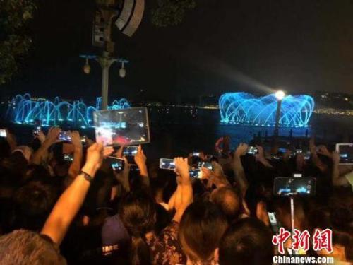 游客用手机记录下音乐喷泉的美丽瞬间。 孙妮亚 摄