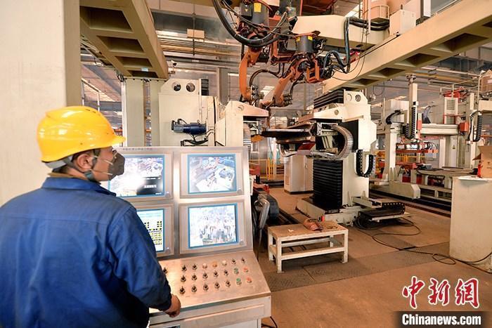 资料图:车间内工作人员进行机器操作。中新社记者 李佩珊 摄