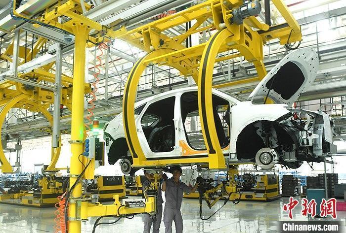 资料图:汽车生产车间内的工作人员正在组装车辆。 中新社记者 陈超 摄
