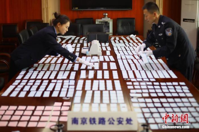 资料图:12月10日,南京铁路公安处民警清点缴获的假火车票。中新社记者 泱波 摄