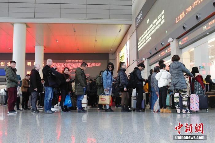 资料图:12月12日,旅客在铁路上海虹桥站排队购买车票。殷立勤 摄