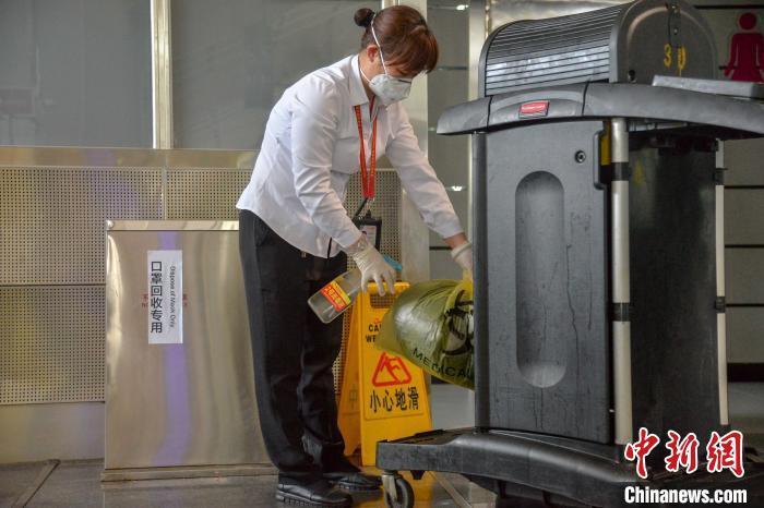 图为14日,海口美兰国际机场清洁工收集口罩后消毒。