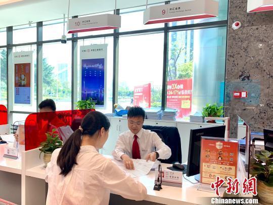 資料圖:銀行工作人員正在為客戶服務。 趙玎 攝