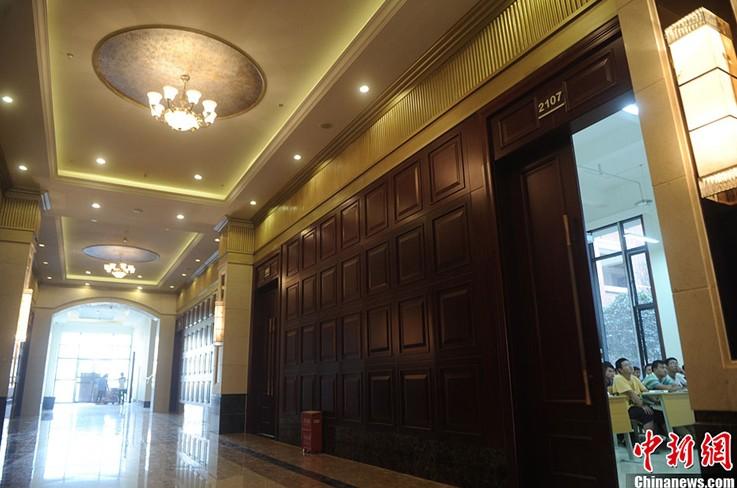 走廊墙面是深色实木装饰